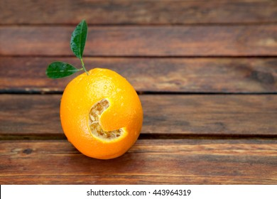 Fresh orange with letter C cut into it resembling vitamin C placed on wooden table