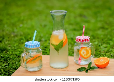 Fresh orange and mint aromatic water in glass on table