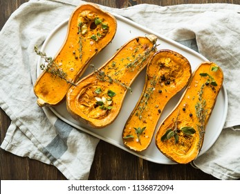 Fresh orange muscat pumpkin cut in half, baked with spices and herbs on an oval ceramic plate. Top view