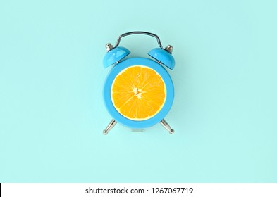 Fresh orange slice in small blue alarm clock