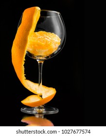 Fresh orange with twisted or swirled orange peels in the wine glass on black background. The idea of pure natural orange juice.
