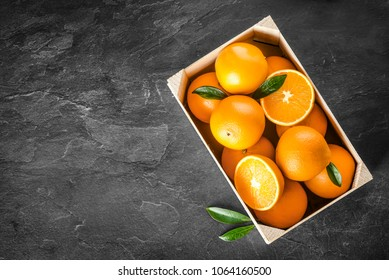 Fresh oranges in basket or wooden box. Oranges on dark stone table. Pile of oranges top view.
