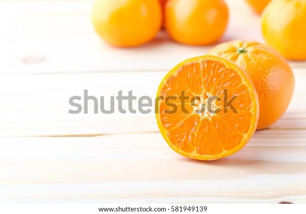 Fresh oranges cut on wooden background