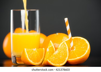 Fresh Oranges with a drinking straw on slate plate. Fresh juice is poured into a glass.