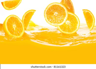 Fresh oranges falling in juice on white background