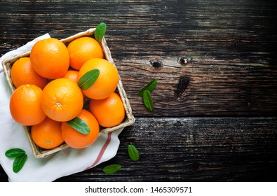 Fresh oranges fruit in wooden basket. Pile of oranges top view.