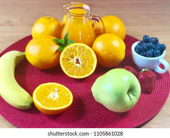 Fresh oranges with juice, blueberries, apple and banana