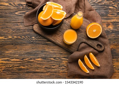Fresh oranges with juice on wooden table