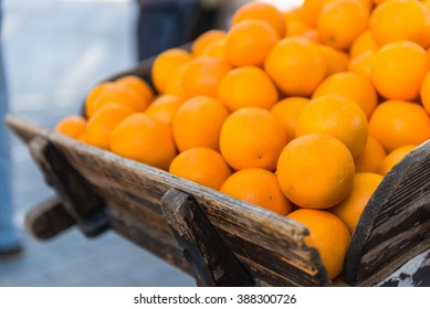 Fresh oranges on vintage wooden cart in the town