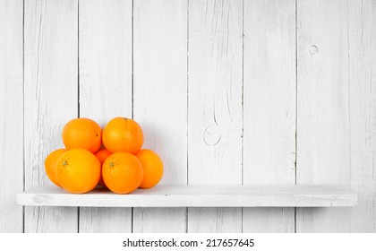 Fresh oranges on wooden shelf.