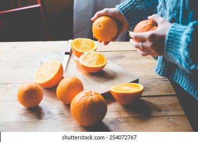 Fresh oranges on wooden table. Toned picture. Selective focus point on cutted orange