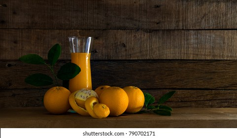 Fresh Oranges and orange juice in jar on wooden table and wood backgrond