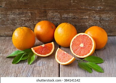 Fresh oranges with slices and leaves on wooden background.
