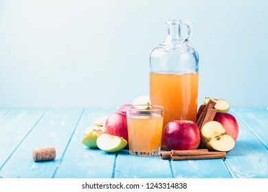 Fresh organic apple cider or apple juice with with cinnamon on the blue background.