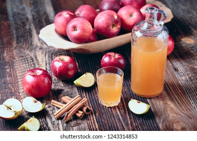 Fresh organic apple cider or apple juice with cinnamon on the old a wooden table.