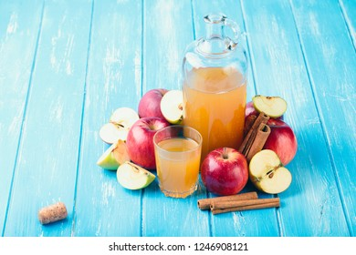 Fresh organic apple cider or apple juice with on the blue background.