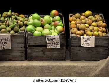 Fresh organic apples and pears in wooden crates on market stand