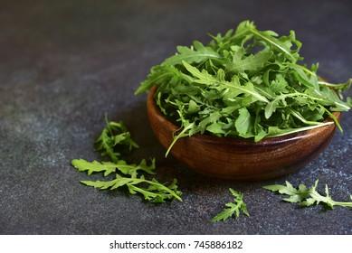 Fresh organic arugula leaves in a wooden bowl on a dark green slate,stone or concrete background.