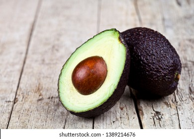 Fresh organic avocado halves on old wooden table background. Fresh avocado halves on rustic wooden backround. Healthy food concept with copy space.