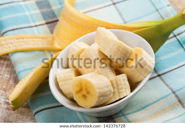 Fresh organic banana in bowl  on wooden background. Selective focus. Rustic style.