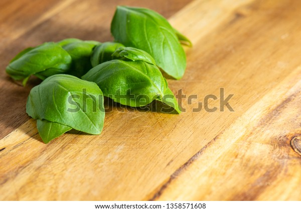 Fresh organic basilic leaves on a wooden surface
