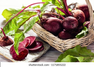 Fresh organic beetroot with green leaves in a basket on a  wnite wooden table.