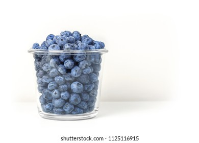 Fresh organic blueberries in transparent glass bowl isolated on white background. Sweet tasty bilberries in pot. Summer seasonal natural vitamines and antioxidants. Healthy diet and nutrition concept.