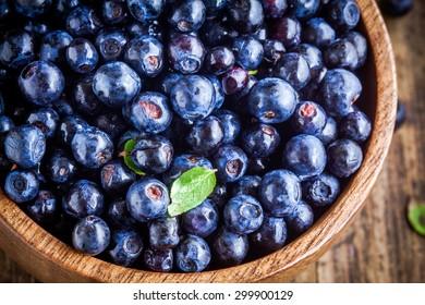 Fresh organic blueberries in a wooden bowl closeup