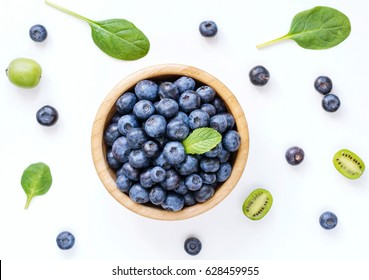 Fresh organic blueberries in wooden bowl, baby kiwi and baby spinach leaf on white background, top view. Flat lay or food pattern.
