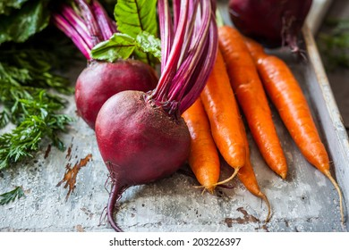 Fresh organic carrots and beetroot  on old wooden board