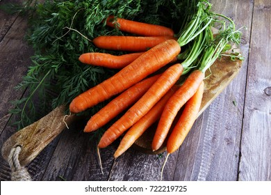 Fresh organic carrots with green leaves on wooden background. Vegetables. Healthy food concept
