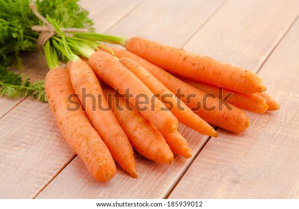 Fresh organic carrots with tops on wooden background