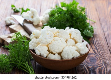 Fresh organic cauliflower cut into small pieces in ceramic bowl on wooden background
