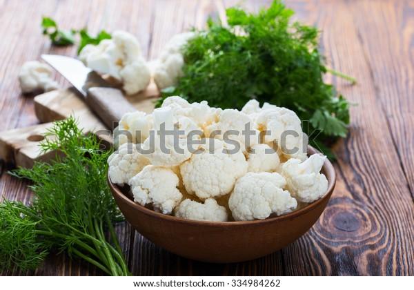 木の背景に新鮮な有機カリフラワーを陶器の鉢で小片に切り分ける