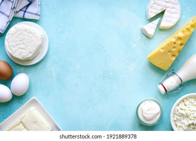 Fresh organic dairy products : butter, eggs, milk, cheese, cream on a light blue slate, stone or concrete background. Top view with copy space.
