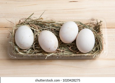 Fresh organic duck eggs, unclean, placing on straw in plastic box on wooden background.