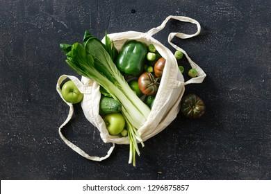 Fresh Organic Food Vegetables and Fruit In Fabric Eco Bag. Vegetarian Or Vegan Food On Dark Background Top View Flat Lay