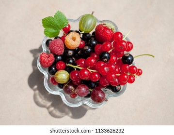 fresh organic fruits in a glass bowl on a stone background