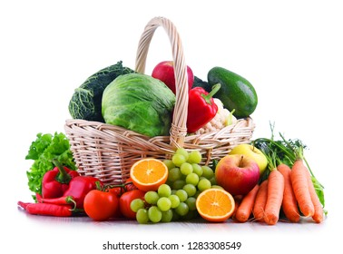 Fresh organic fruits and vegetables in wicker basket isolated on white