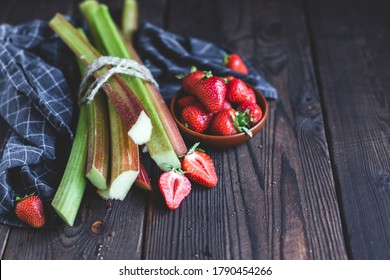 Fresh organic garden strawberries and rhubarb stems on wooden background. Flat lay. Still life.Ingredients for summer lemonade, jam or cake