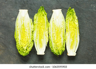 Fresh organic gem lettuces on a slate background