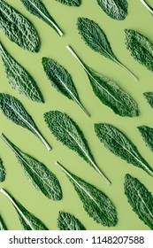 Fresh organic green kale leaves pattern on a green background, flat lay healthy nutrition concept