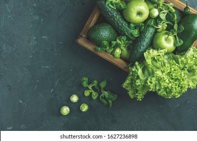 Fresh organic green vegetables and fruits on green background. Spring diet, healthy raw vegetarian, vegan concept, detox breakfast, alkaline clean eating. Copy space.