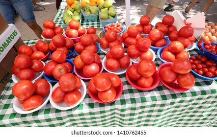 Fresh, organic, hand-picked ripe tomatoes for sale at a local farmer's market.