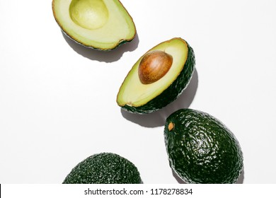 Fresh organic hass avocados on a white background, creative flat lay healthy food concept