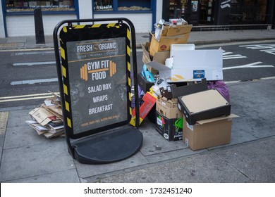 Fresh organic healthy eating sign sitting next to a pile of rubbish on a central London street. London - 18th September 2019