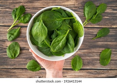 Fresh Organic Healthy Spinach in White Bowl Overhead Shot with White Female Hands Holding White Bowl on Wood Texture Table Background