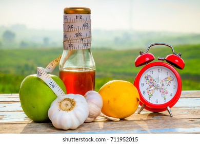 Fresh organic honey in glass jar , measuring tape, green epal , lemon ,garlic and alarm clock on old wooden with blurred background ,healthy nutrition,strengthening immunity, diet and treatment of flu