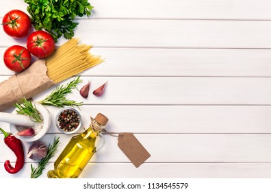 Fresh organic ingridients, pasta spaghetti of italian recipes. Olive oil with tag. Healthy food concept on white wooden table background. Top view, copy space.
