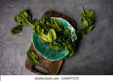 Fresh organic leaves of baby spinach on rustic background with copy space as a organic food concept